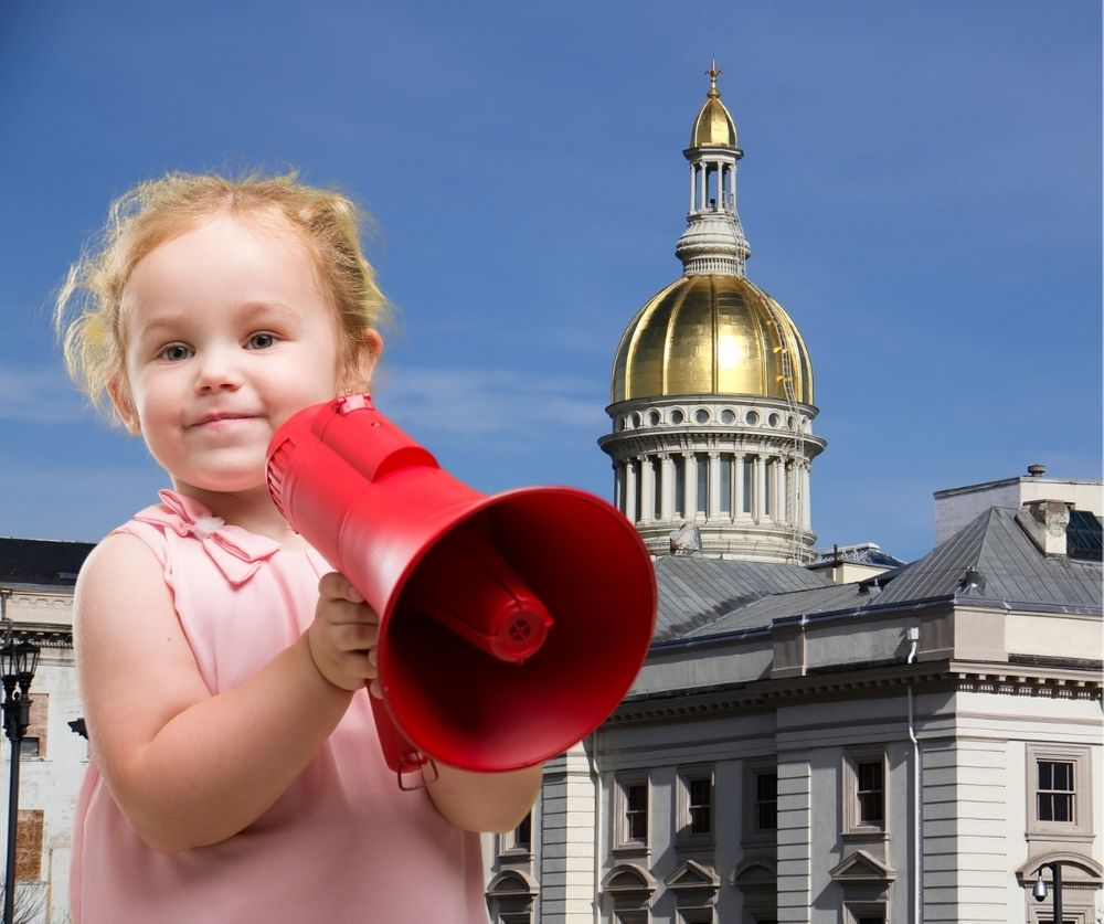 Blonde toddler with megaphone in front of statehouse