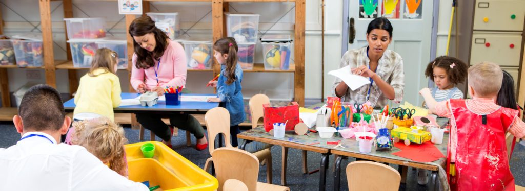 Class of nursery children doing arts and crafts with their teachers. They are using recycled boxes and cartons.